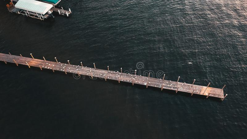 Aerial shot of a long wooden pier and amazing texture of the water. An aerial shot of a long wooden pier and amazing texture of the water stock images