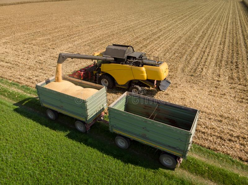 Aerial shot of harvester loading off corn on trailers. Aerial shot of modern harvester loading off corn on tractor trailers stock photography