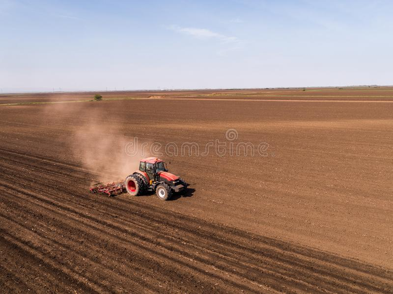 Aerial shot of a tractor cultivating field at spring royalty free stock images