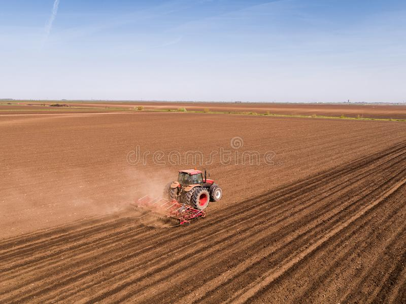 Aerial shot of a tractor cultivating field at spring royalty free stock photo