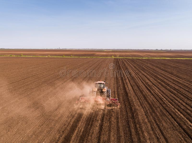 Aerial shot of a tractor cultivating field at spring stock image