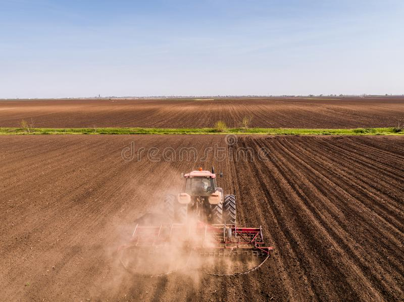 Aerial shot of a tractor cultivating field at spring stock images