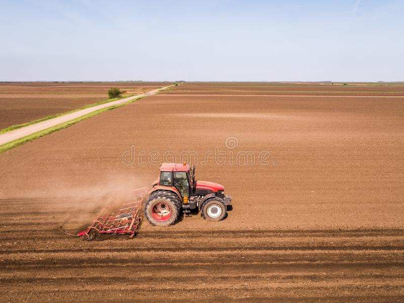 Aerial shot of a tractor cultivating field at spring royalty free stock photography