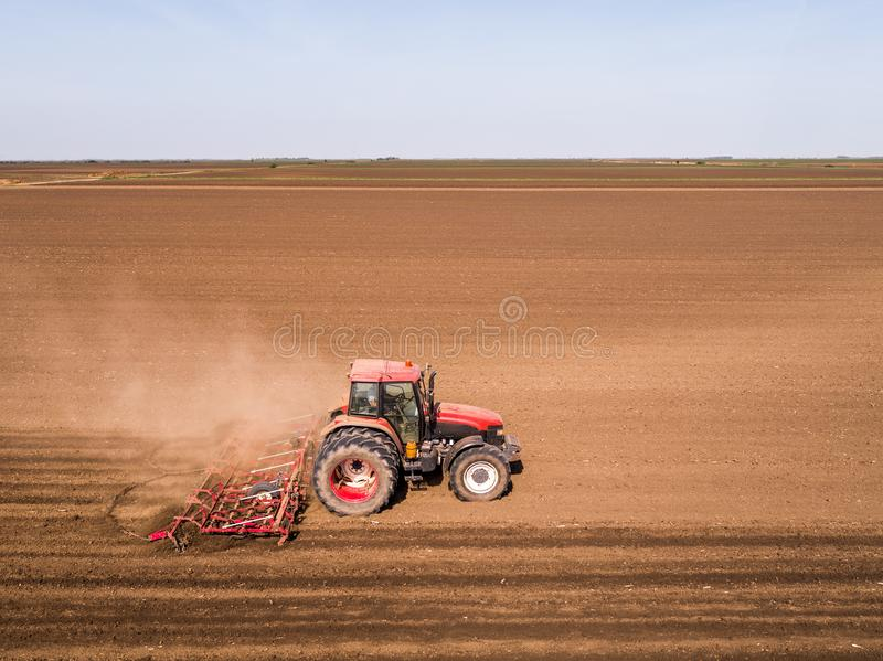 Aerial shot of a tractor cultivating field at spring stock photo
