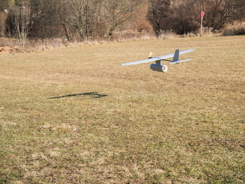 Drone airplane, low altitude passage. Aerial spy drone, passage at low altitude, on meadow, trees background royalty free stock photography