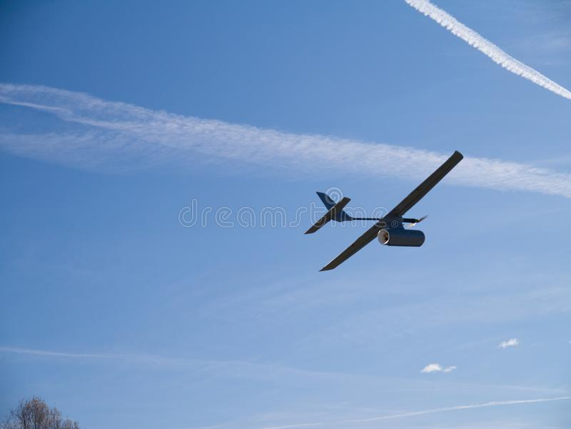 Drone airplane, low altitude passage, sunny sky with clouds. Aerial spy drone, passage at low altitude, sunny sky with clouds stock photography