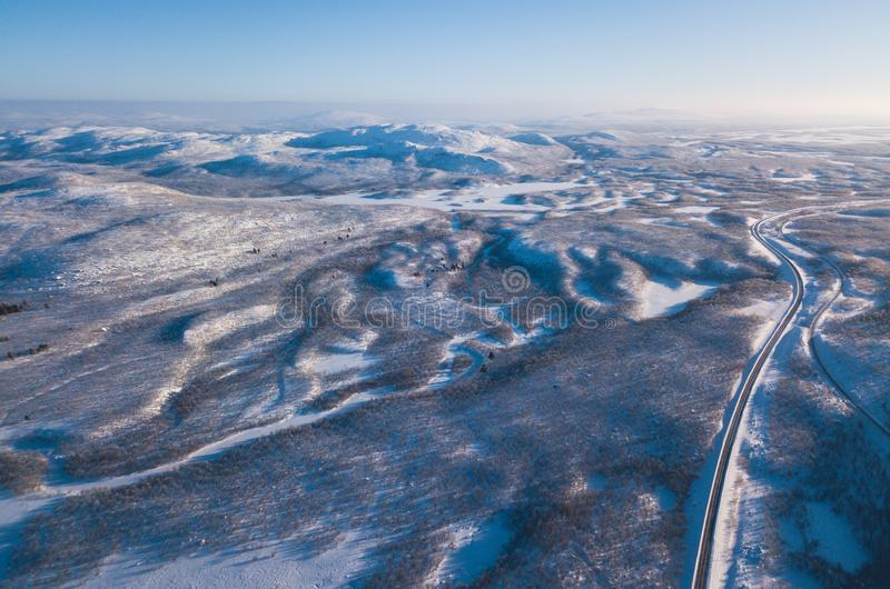 Aerial sunny winter view of Abisko National Park, Kiruna Municipality, Lapland, Norrbotten County, Sweden, shot from drone, with r. Oad and mountains stock photo