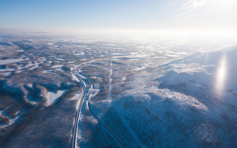 Aerial sunny winter view of Abisko National Park, Kiruna Municipality, Lapland, Norrbotten County, Sweden, shot from drone, with r. Oad and mountains stock image