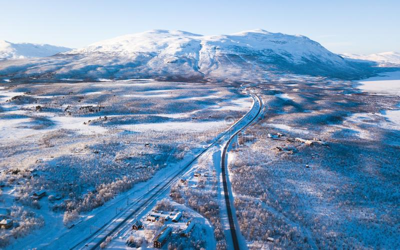 Aerial sunny winter view of Abisko National Park, Kiruna Municipality, Lapland, Norrbotten County, Sweden, shot from drone, with r. Oad and mountains royalty free stock photography