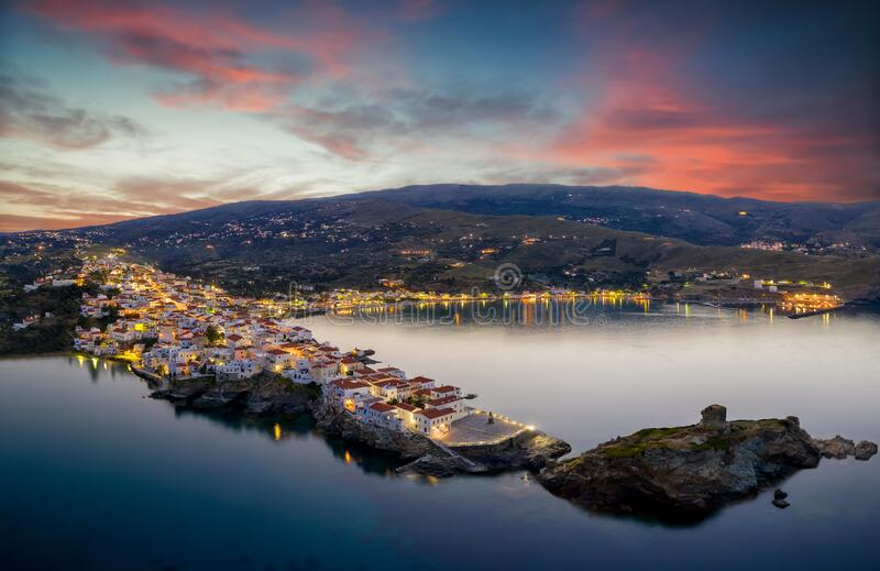 Aerial sunset view of the beautiful illuminated town of Andros island, Cyclades, Greece stock photos