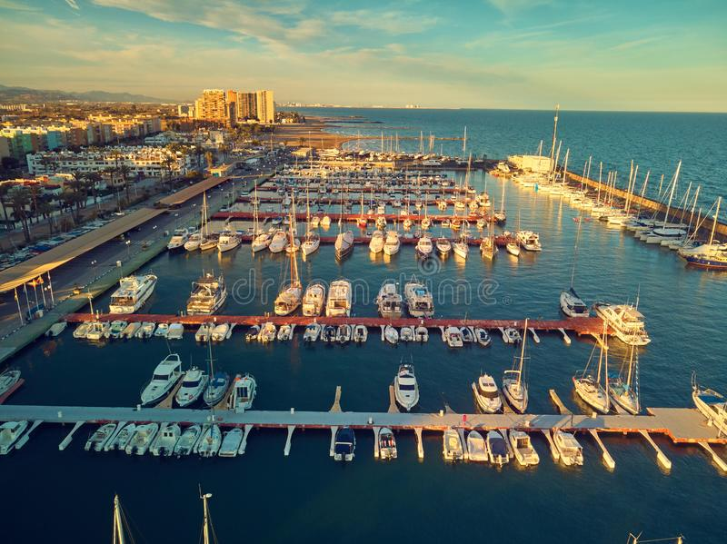 Aerial sunset view of the marina of La Pobla de Farnals, Valencia, Spain. Boats moored in the harbor at sunset of the stock image