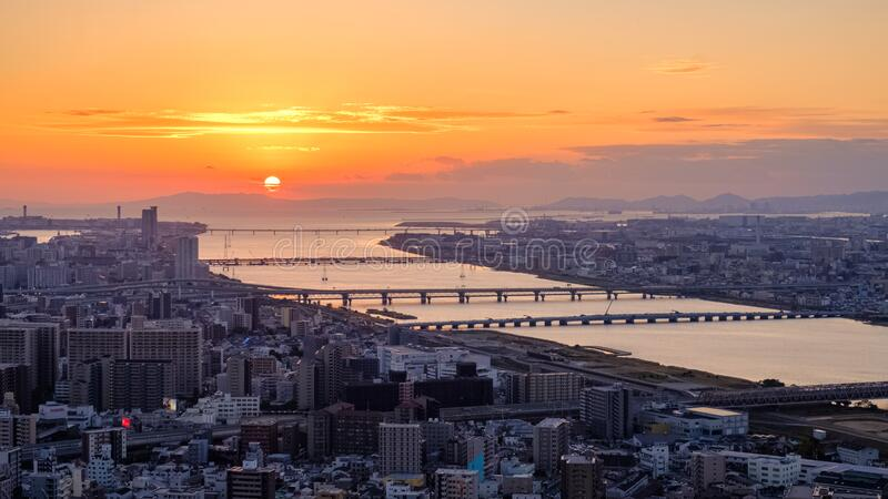 Aerial sunset view of Osaka skyline with the river, round sun, and golden sky as seen from Umeda Sky Building. Observation Deck royalty free stock photos