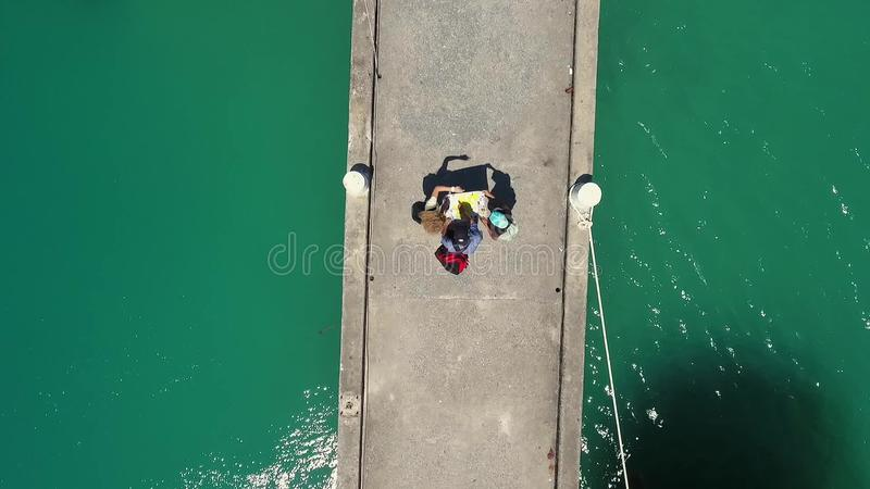 Aerial: Three Young Mixed Race Tourists Reading Street City Map on a Pier. Koh Phangan, Thailand. HD stock footage