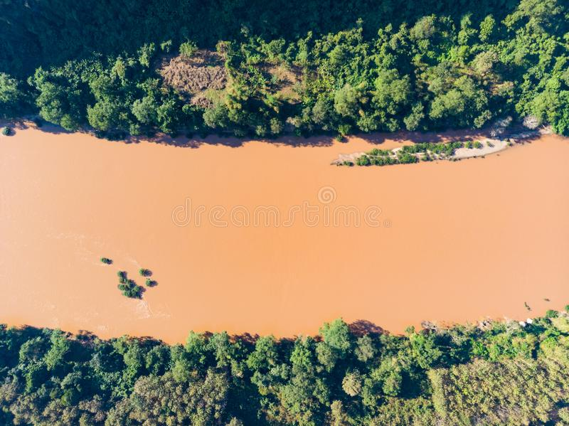 Aerial top down Nam Ou River Nong Khiaw Muang Ngoi Laos, red brown water flowing through forest, famous travel destination in royalty free stock photo