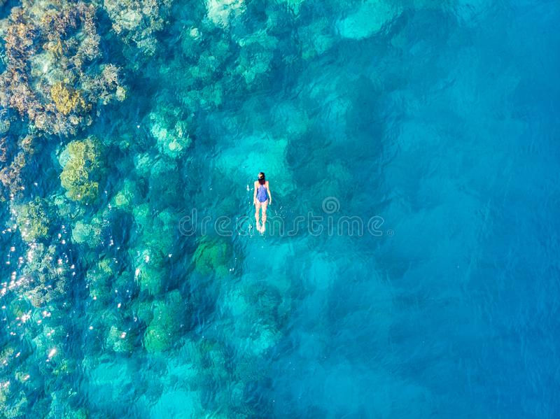 Aerial top down people snorkeling on coral reef tropical caribbean sea, turquoise blue water. Indonesia Banyak Islands Sumatra, stock photography