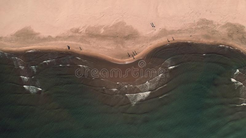 Aerial top down view of sea surf on sand beach and walking people. Aerial top down shot of sea surf on sand beach stock photos