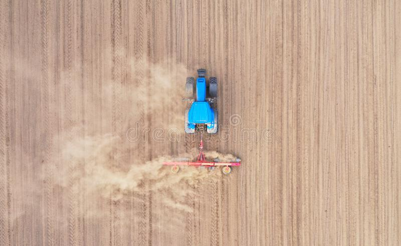 Aerial top down view on blue tractor pulling a plow, preparing a soil for seed sowing, tractor making dirt cloud royalty free stock photos