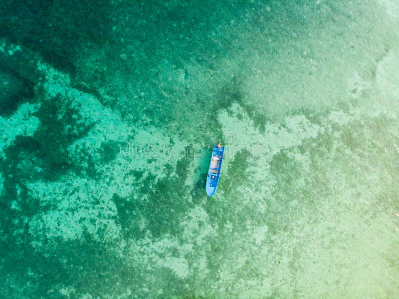 Aerial top down view boat canoe floating on turquoise coral reef tropical caribbean sea. Indonesia Moluccas archipelago, Kei stock photo