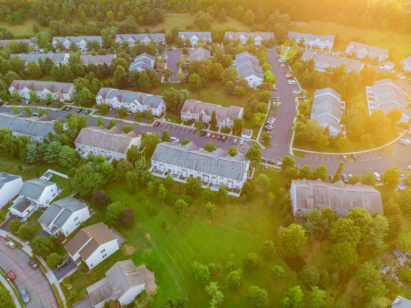 Aerial top down view flying over appartments in small town showing neighborhood early sunrise royalty free stock images