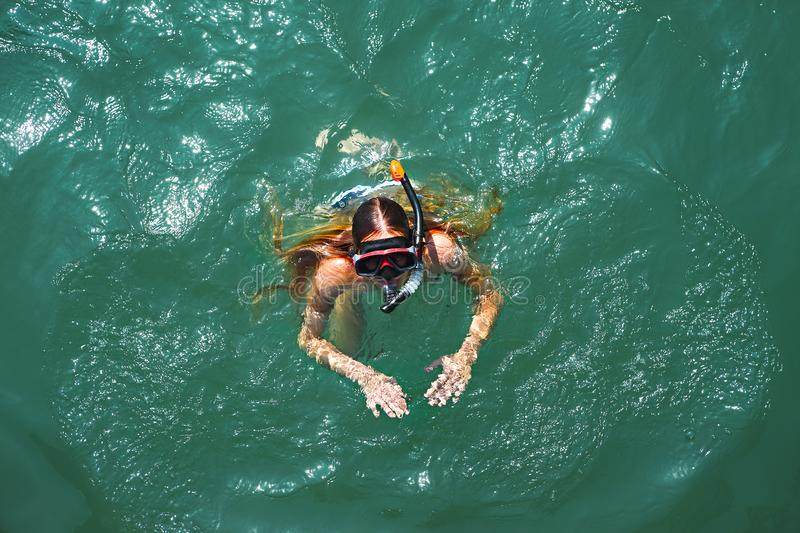 Aerial top down view of a girl wearing swimming mask in the sea stock images