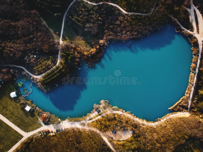 Aerial top down view of pond or lake for fishing in spring mountain forest with pathways, drone shot royalty free stock photos