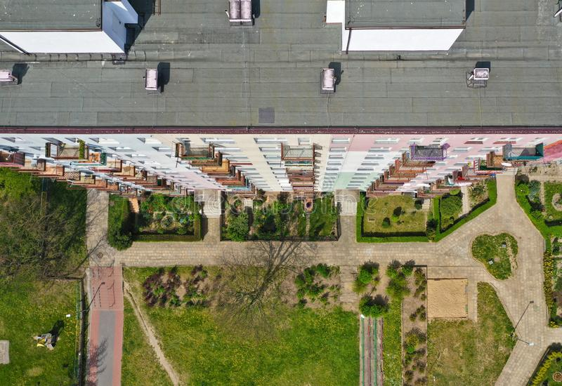 Aerial top down view on rooftop of block flat building with yard, pavements, gardens, multiple windows and balcony stock photo