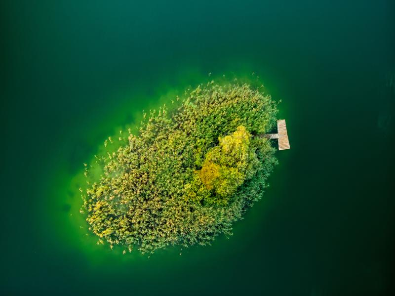 Aerial top down view of small island. Birds eye view of beautiful green waters of lake Gela surrounded by pine forests. stock photography