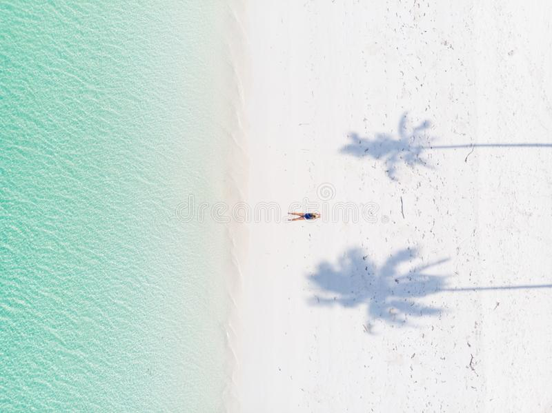 Aerial top down view tropical beach caribbean sea. Woman sunbathing between palm tree shade on white sand beach turquoise water. stock photos