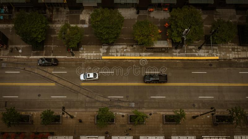 Aerial Top down view of vehicles driving down a city street stock image