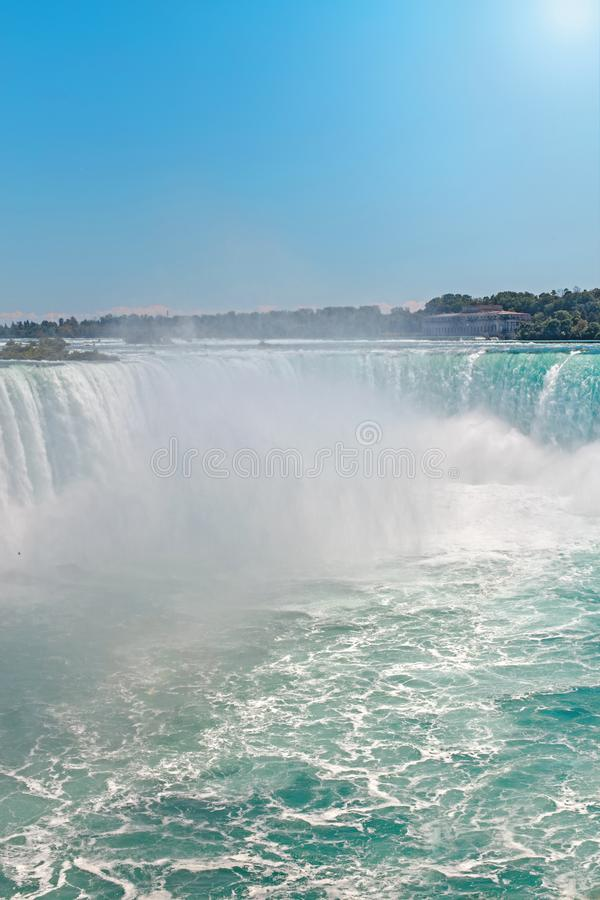 Aerial top landscape view of Niagara Falls  between United States of America and Canada. Horseshoe of Canadian waterfall on sunny day. Water tour boat at stock photo