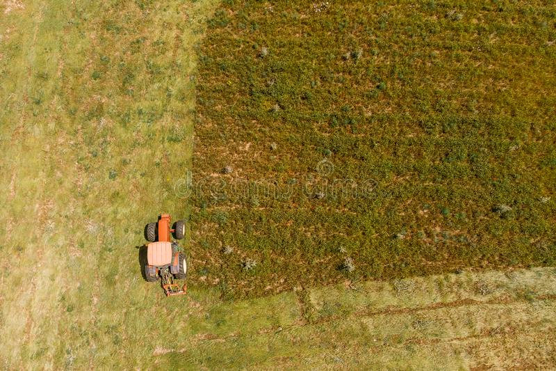 Aerial top view agriculture, tractor removes mowing green grass field royalty free stock photography