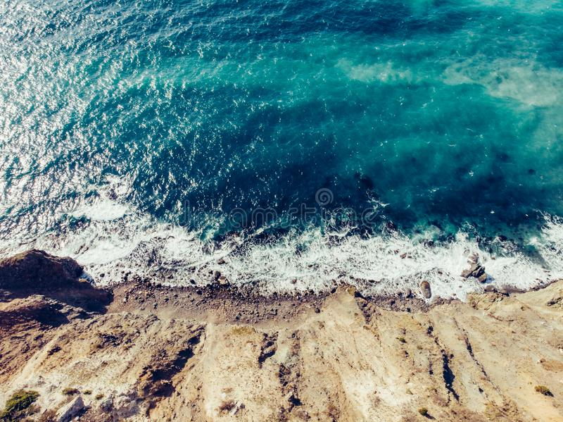 Aerial top view of azure sea water with waves at sand coastline, beautiful summer tropical ocean background with copy space royalty free stock image