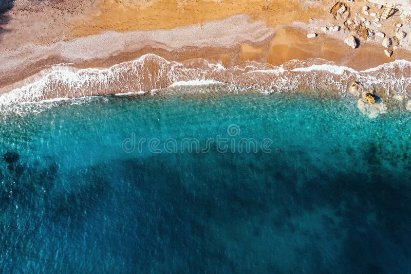 Aerial top view of azure sea waves and sandy beach coast in sunny summer day, drone photo royalty free stock image