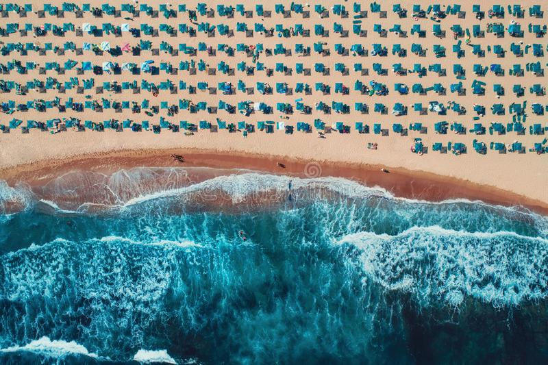 Aerial top view on the beach. Umbrellas, sand and sea waves stock image