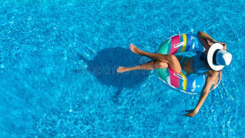 Aerial top view of beautiful girl in swimming pool from above, relax swim on inflatable ring donut and has fun in water. On family vacation, tropical holiday stock photos