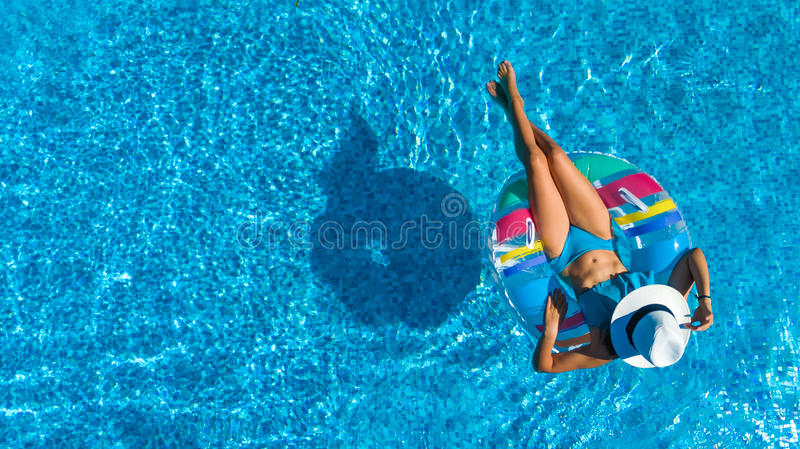 Aerial top view of beautiful girl in swimming pool from above, relax swim on inflatable ring donut in water on family. Aerial top view of beautiful girl in royalty free stock photography