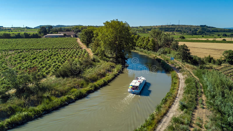 Aerial top view of boat in Canal du Midi from above, travel by barge in Southern France stock photos