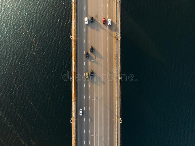 Aerial or top view of bridge with asphalt road or highway over big river with city car traffic, urban transportation stock images