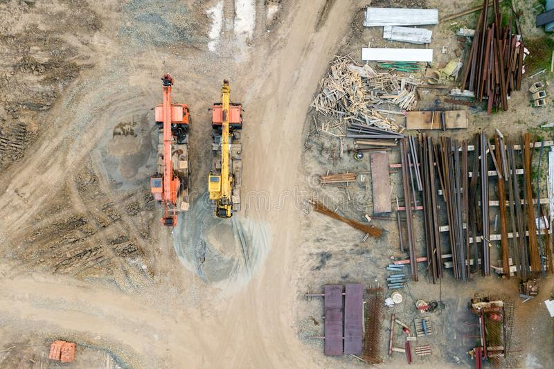 Aerial top view: constraction crane or trucks. Go together country road on the construction site to start construction of a new residential complex in the new royalty free stock image