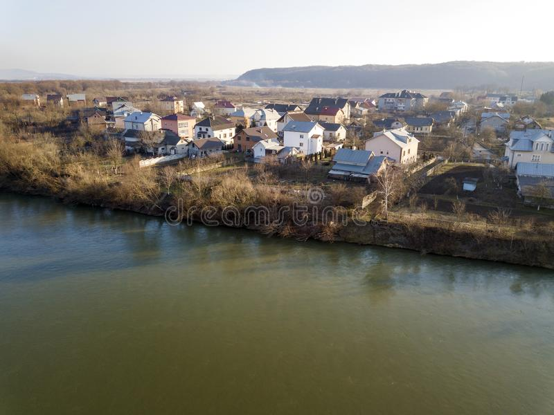 Aerial top view, countryside panorama of residential houses on river bank on blue sky and woody hill background. Drone photography stock photo