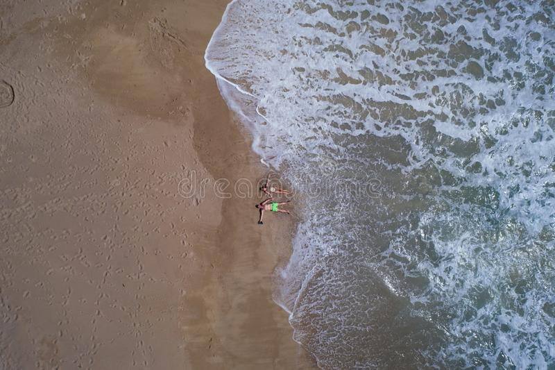 Aerial top view of couple laying on the sandy beach royalty free stock photos
