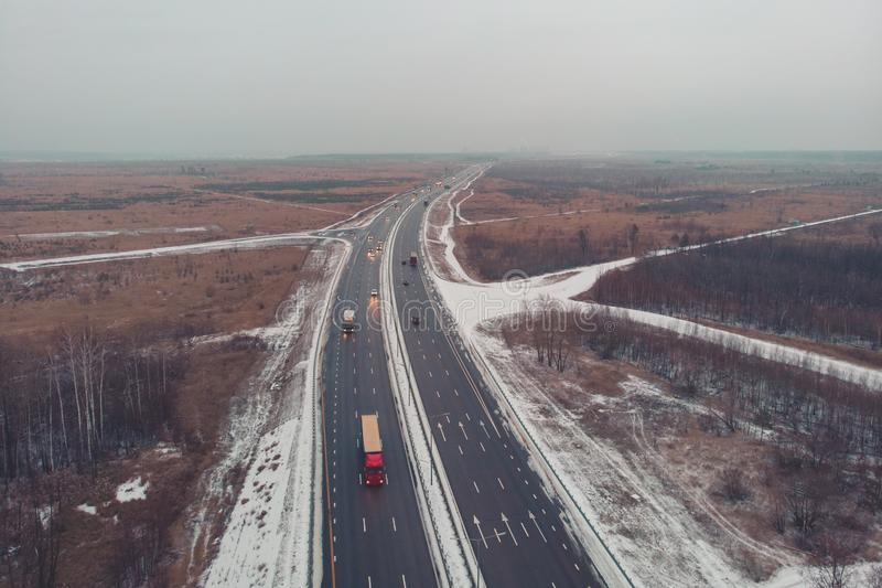 Aerial or top view from drone to winter asphalt highway or motorway road in countryside with cargo logistic trucks traffic royalty free stock photo