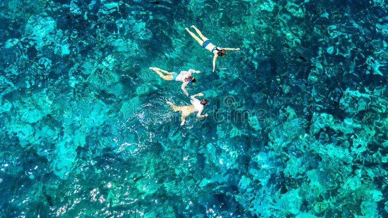 Aerial top view of family snorkeling from above, mother and kids snorkelers swimming in a clear tropical sea water with corals. During summer vacation in stock images