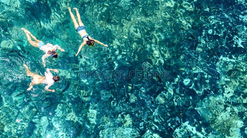 Aerial top view of family snorkeling from above, mother and kids snorkelers swimming in a clear tropical sea water, Thailand royalty free stock image