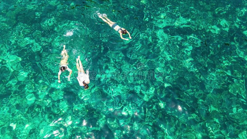 Aerial top view of family snorkeling from above, mother and kids snorkelers swimming in a clear tropical sea water, Thailand stock images