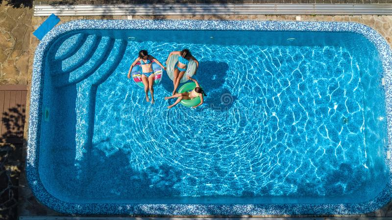Aerial top view of family in swimming pool from above, mother and kids swim on inflatable ring donuts and have fun in water. Aerial top view of family in royalty free stock photos
