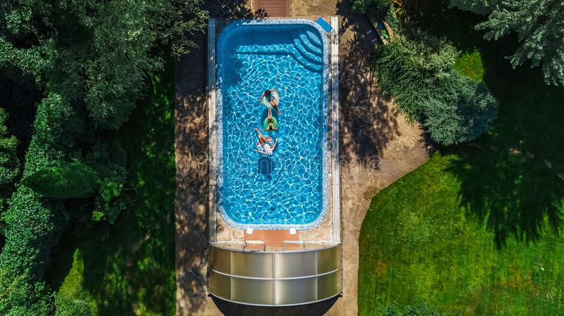Aerial top view of family in swimming pool from above, happy mother and kids swim on inflatable ring donuts and have fun in water. On family vacation, tropical stock photo