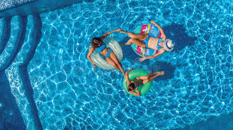 Aerial top view of family in swimming pool from above, happy mother and kids swim on inflatable ring donuts and have fun in water. On family vacation stock images