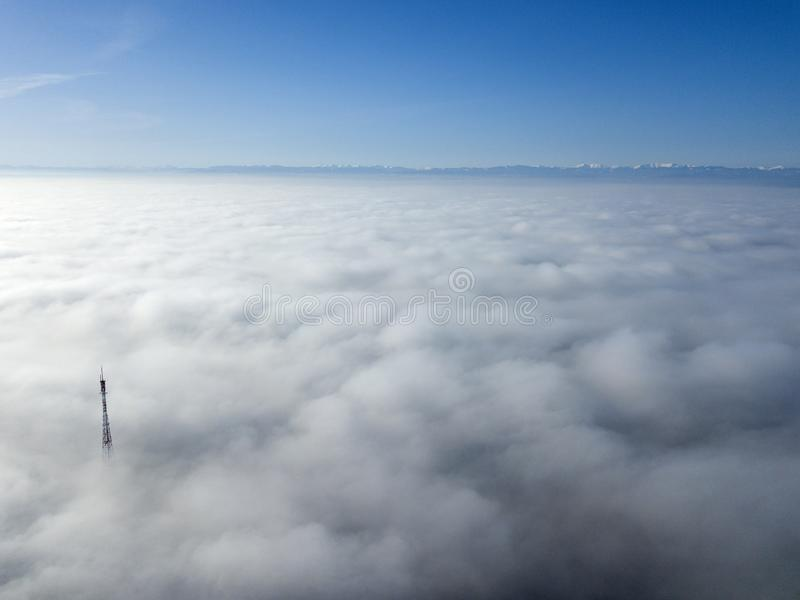 Aerial top view of foggy cloudy landscape with radio or TV antenna top on blue sky copy space background and mountain ridge on royalty free stock images