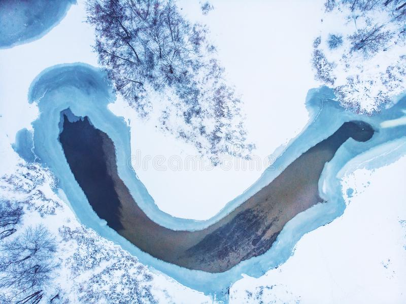 Aerial top view of frozen lake among snow winter landscape, abstract nature background royalty free stock image
